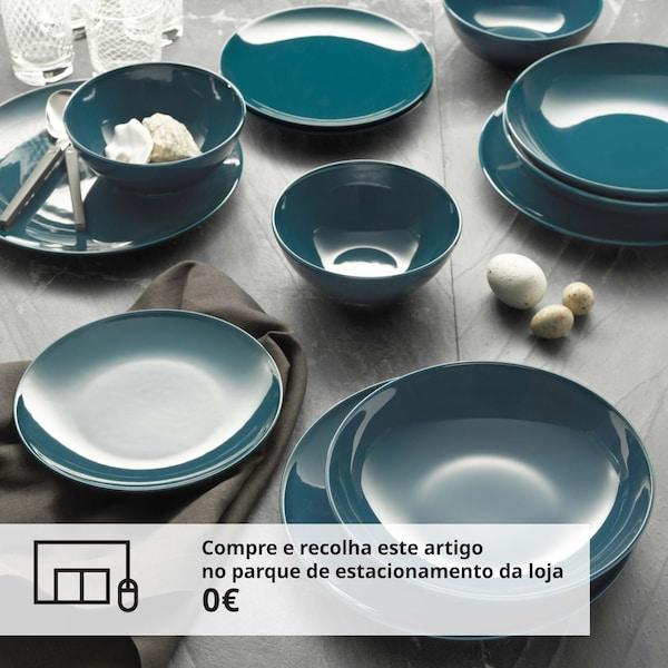 Pormenor de vários pratos de refeição, de sobremesa e tigelas azuis em cima de uma mesa.