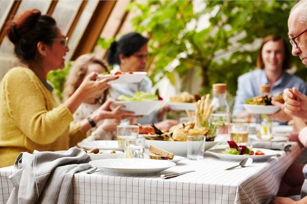 Porodica i prijatelji okupljeni oko stola postavljenog IKEA 365+ setom za ručavanje u beloj boji.