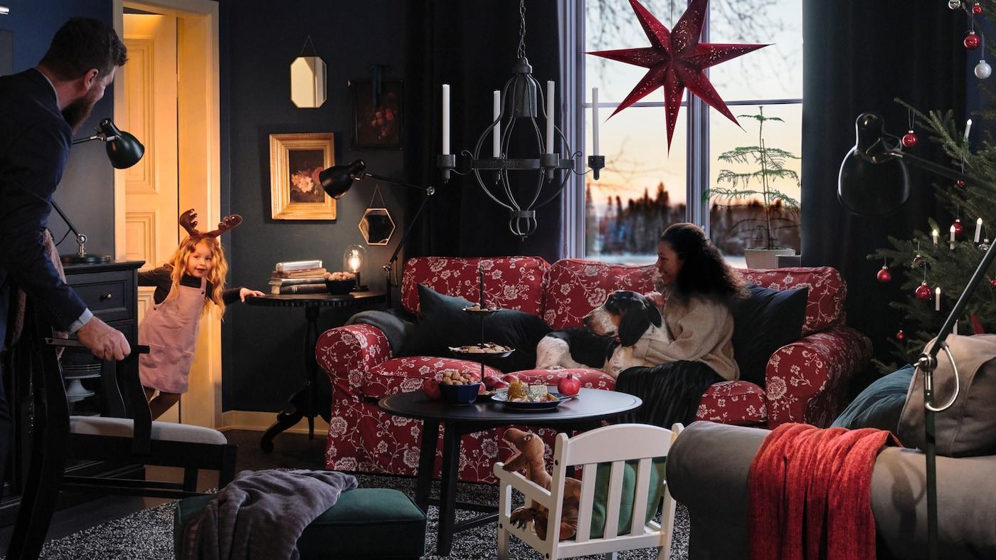 Porodica sedi u dnevnoj sobi zajedno sa psom i čeka da devojčica koja proviruje sa vrata izvede predstavu.