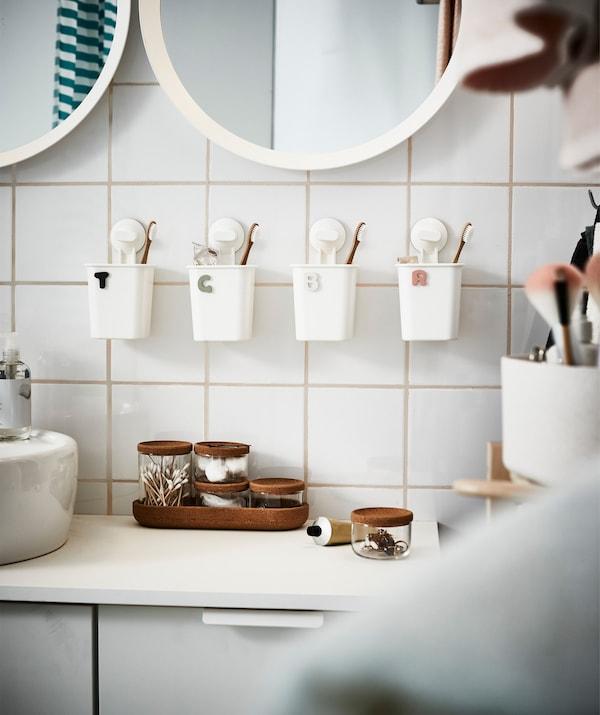 Portacepillos individuais pegados a unha parede de baño con azulexos brancos ao lado dun lavamáns e un espello.
