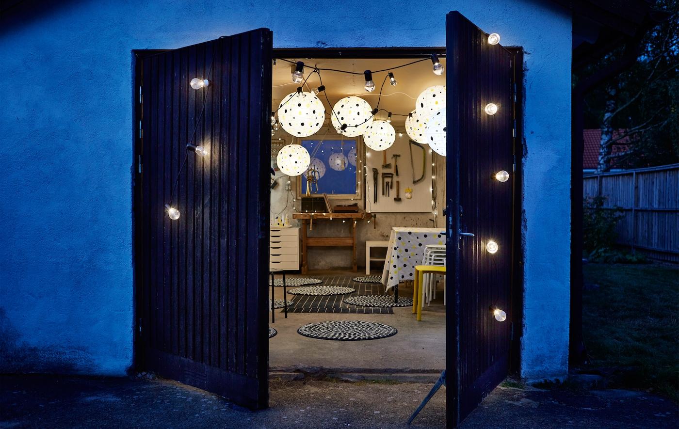 Porte de jardin en bois ornée d'une guirlande lumineuse annonciatrice d'un réveillon festif, avec des lanternes en papier à pois à l'intérieur.