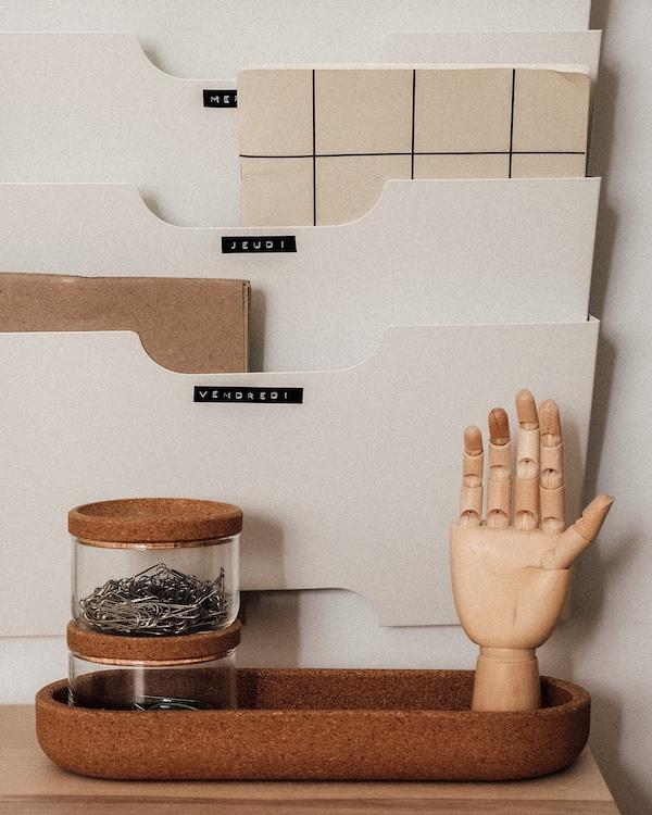 Porte-revues KVISLE et bocaux SAXBORGA avec couvercles en liège, contenant des fournitures de bureau.