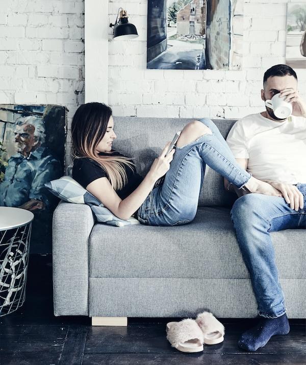 Portret Katarzyne i Mikolaja koji se opuštaju na sivoj sofi ispred bijelog zida od cigle.