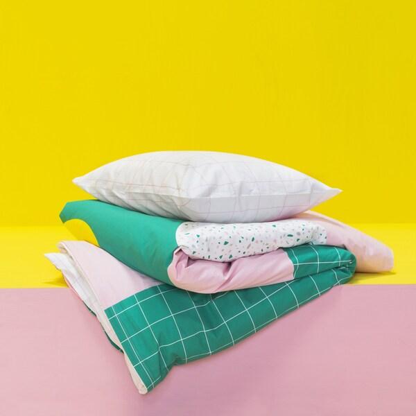 Pościel w różowe i zielone wzory złożona na różowej i żółtej półce.