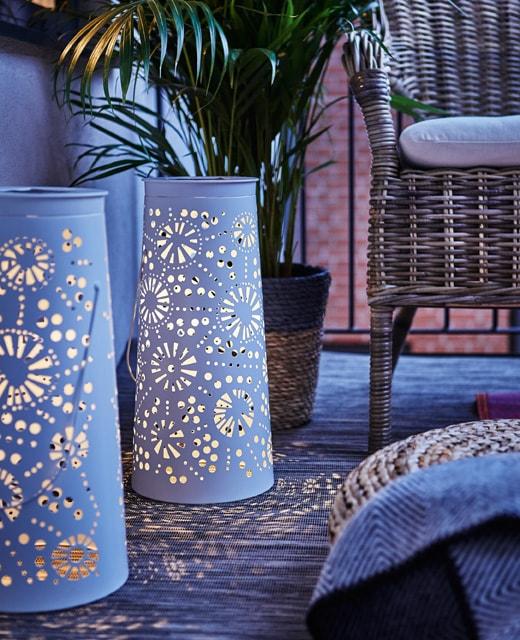 Posées au sol, deux lanternes solaires à DEL en métal blanc illuminent le balcon une fois le soir venu.