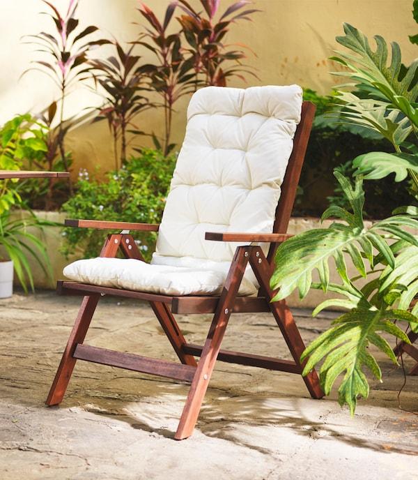 Positionsstol af mørkt træ med hvide hynder, omgivet af planter i et udendørsområde.