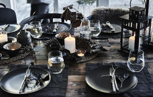 Postav stola s prirodnim materijalima i tamnim posuđem.