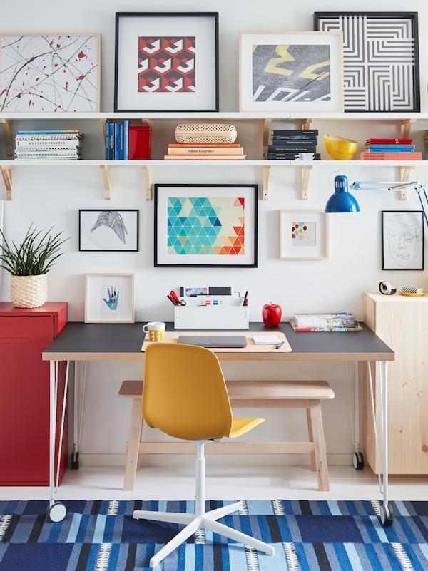 Postazione di lavoro creata con sedia girevole LEIFARNE e tavolo LINNMON/KRILLE con rotelle, accanto a una parete con mensole e immagini incorniciate.