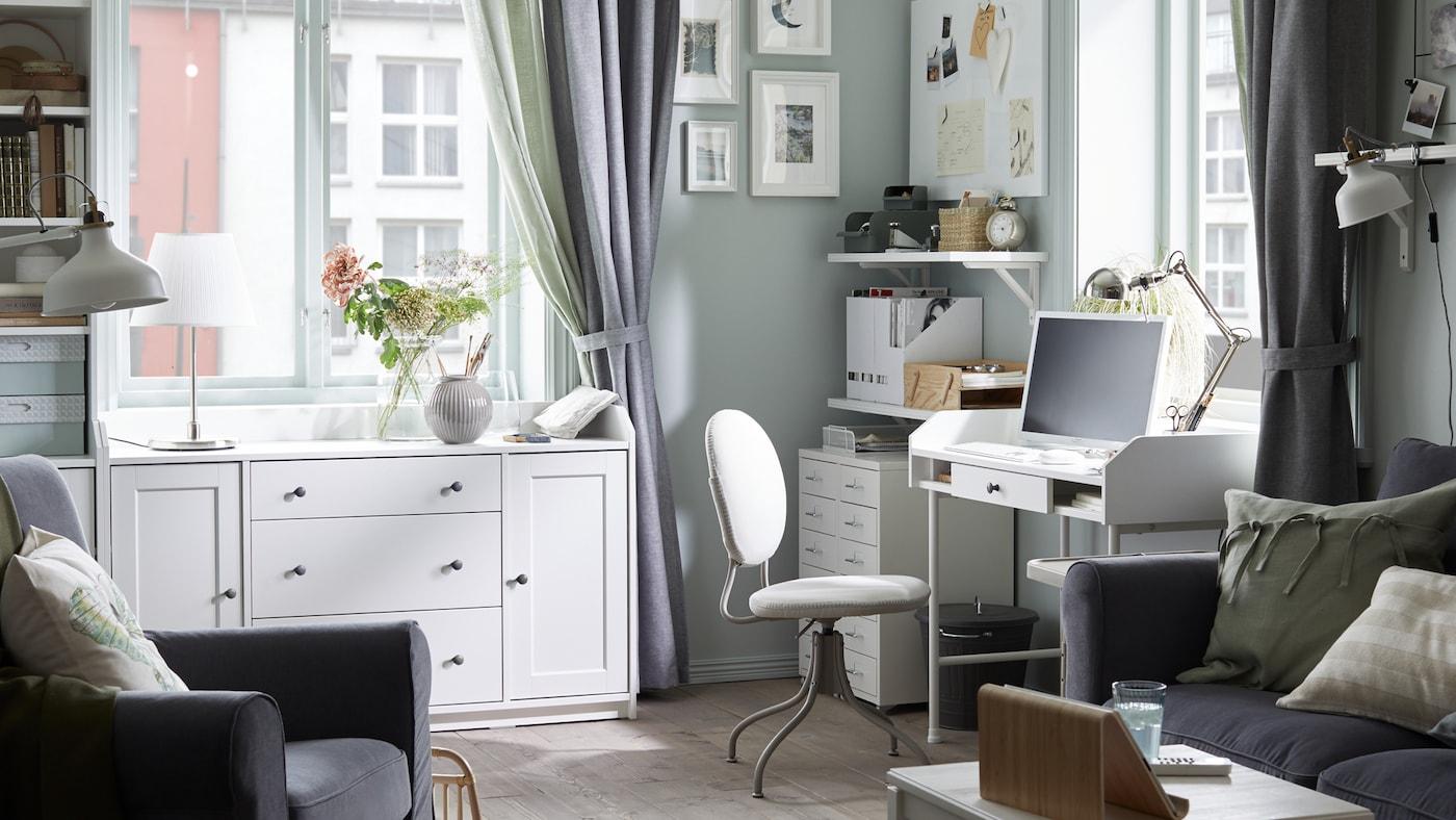 Postazione di lavoro in soggiorno con scrivania bianca, sedia girevole, cassettiere bianche con rotelle e tende grigie.