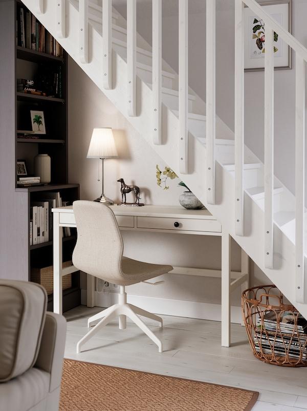 Postazione di lavoro sotto una scala, con scrivania HEMNES bianca, sedia LÅNGFJÄLL, lampada e libreria alta.
