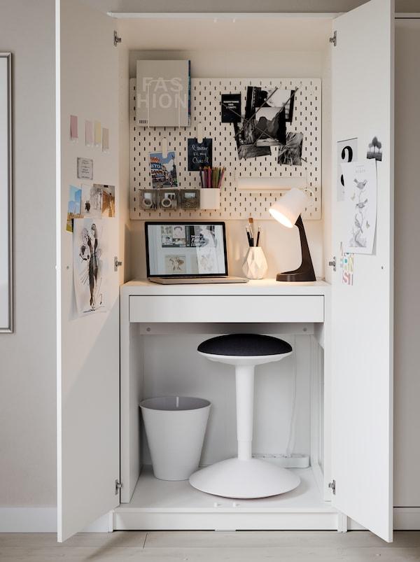 Postazione di lavoro supercompatta creata all'interno di un guardaroba KLEPPSTAD, con scrivania MICKE, sgabello NILSERIK, lampada e pannello portaoggetti.