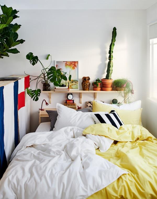 Postel mezi okny, za postelí jsou police s květinami a dekoracemi. Na postelí je bílé a žluté povlečení.