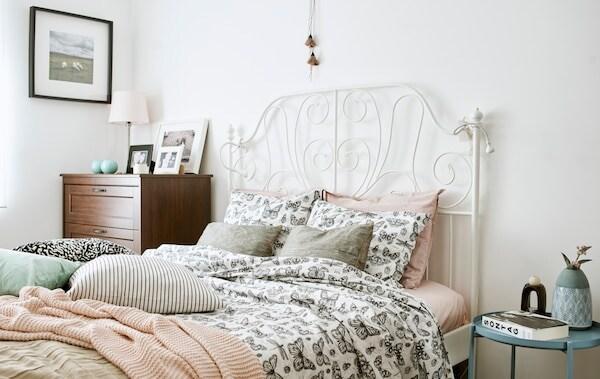 Posteľ s bielym čelom postele zo zvárkovej ocele ustlaná posteľnými obliečkami s motívom čierno-bielych motýľov, ružovou pletenou prikrývkou a vankúšmi.
