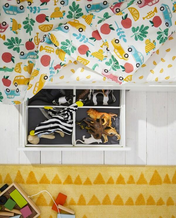 Postelový rám s otevřenou zásuvkou s hračkai uvnitř, žlutý koberec, barevné povlečení a žluto-bílé prostěradlo.