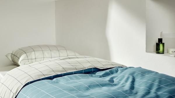 Poszwa VITKLÖVER ułożona na łóżku pojedynczym w sposób ukazujący różne kolory bazowe na każdej stronie.