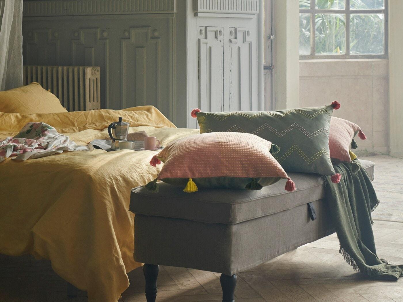 Potahy na polštáře KLARAFINA a MOAKAJSA v růžové a zelené položené na lavici před postelí se žlutým povlečením