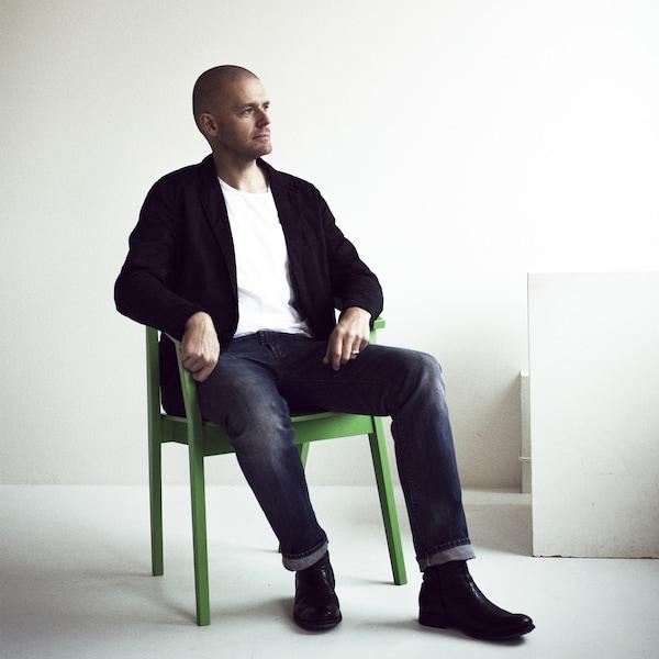 Potret Ola Wihlborg sedang duduk di atas kerusi berwarna hijau.