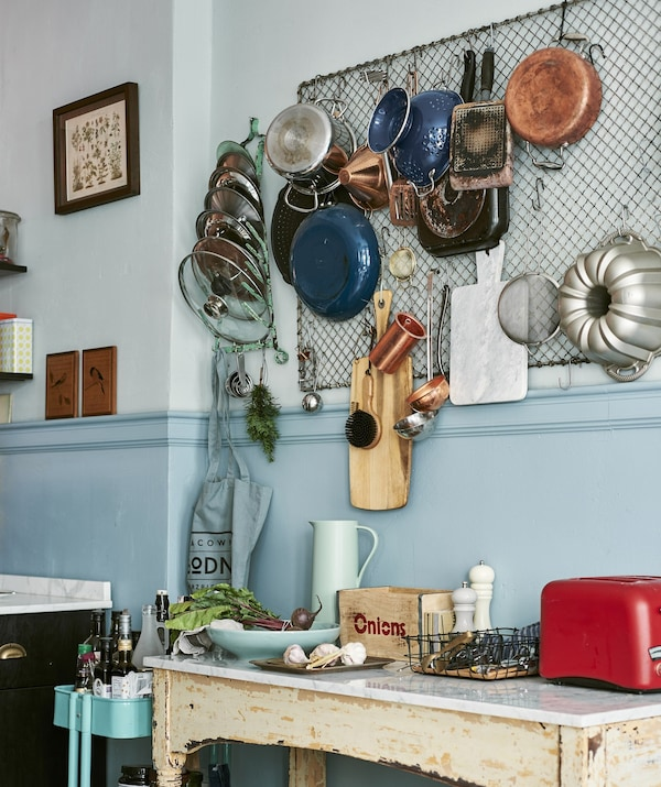 Pots, pans and cooking utensils hanging from large mesh grid on kitchen wall, over a rustic-looking side table.