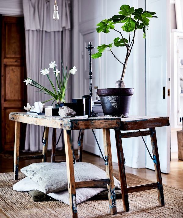 Potted plants and stones on rustic wooden benches.