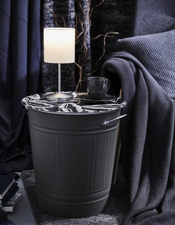 Poubelle KNODD surmontée d'un plateau décoratif, transformée en table d'appoint, avec lampe et tasse de café posées dessus.