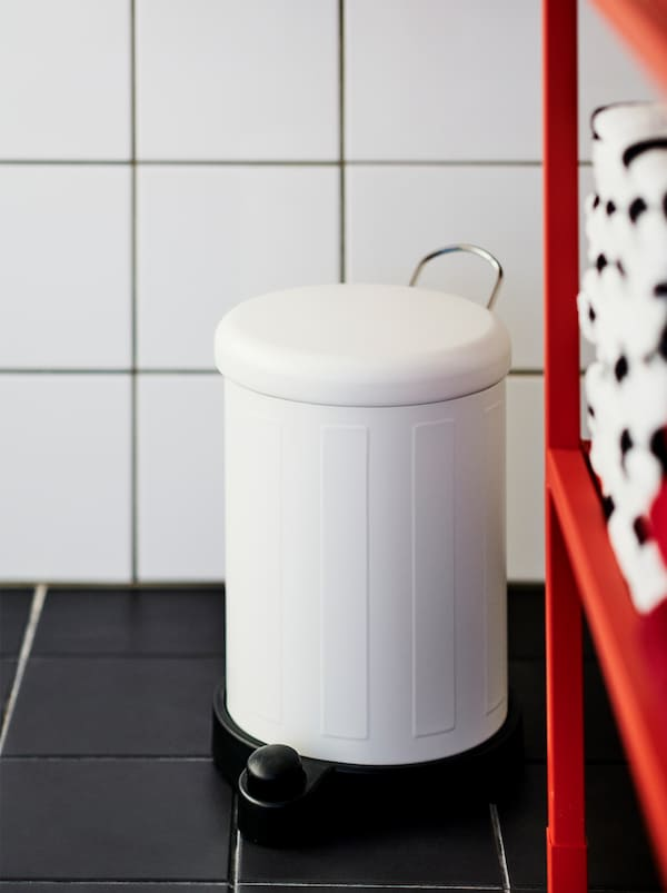 Poubelle TOFTAN blanche dans une salle de bains carrelée aux murs blancs et au plancher noir, près d'une étagère ENHET rouge à rangement ouvert.