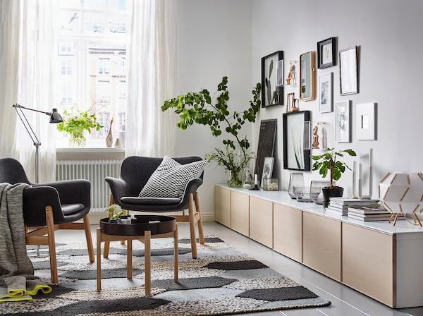Pour à la fois exposer et ranger vos affaires dans le salon une longue rangée de meubles bas BESTÅ en blanc et frêne. Deux fauteuils VEDBO en Gunnared gris et une table basse ont été placés au centre de la pièce.