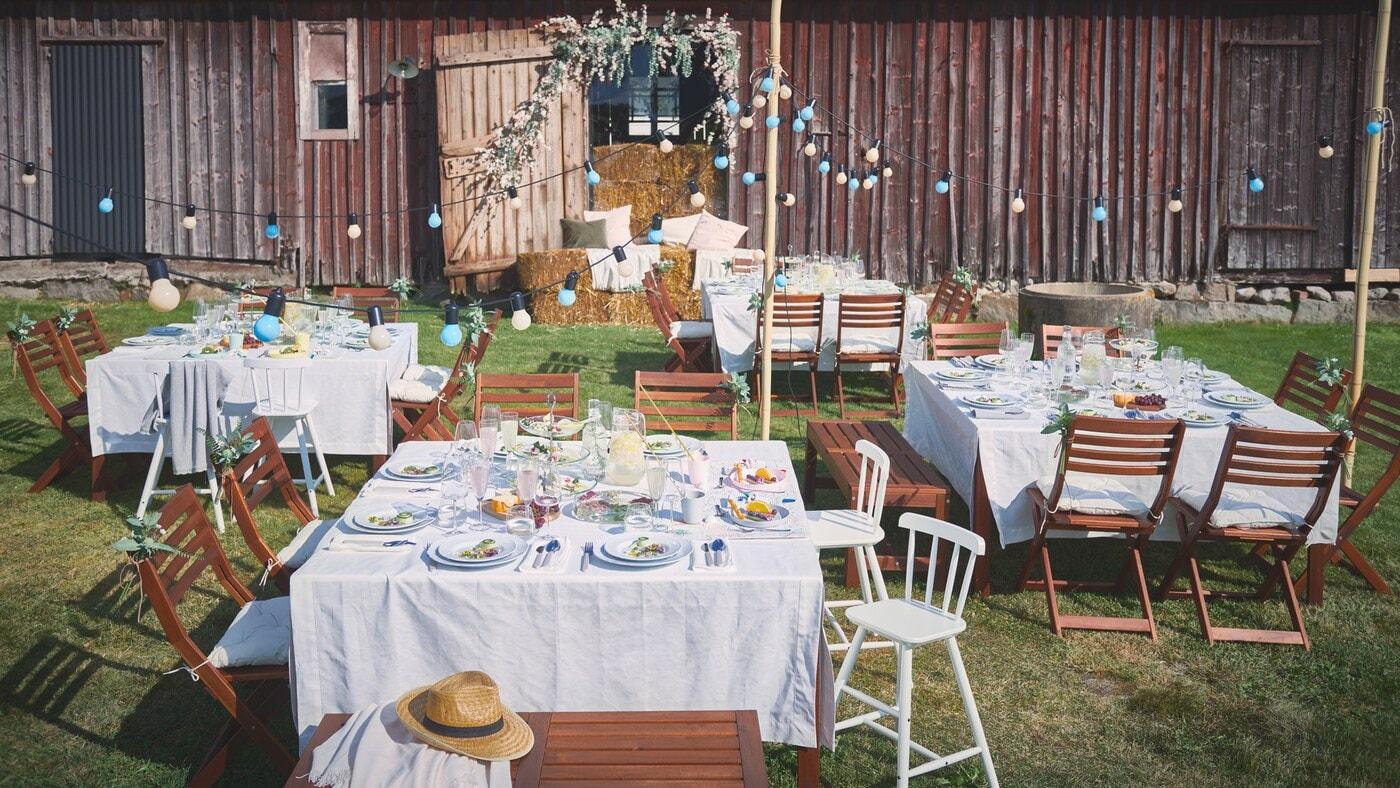 Pour une fête à l'extérieur, des tables sont dressées avec des nappes GULLMAJ, des assiettes UPPLAGA, des verres DYRGRIP et des couverts UPPHÖJD.
