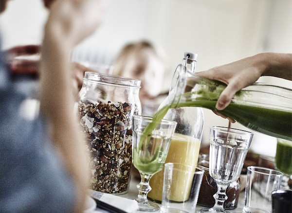 Pouring green juice into a glass.
