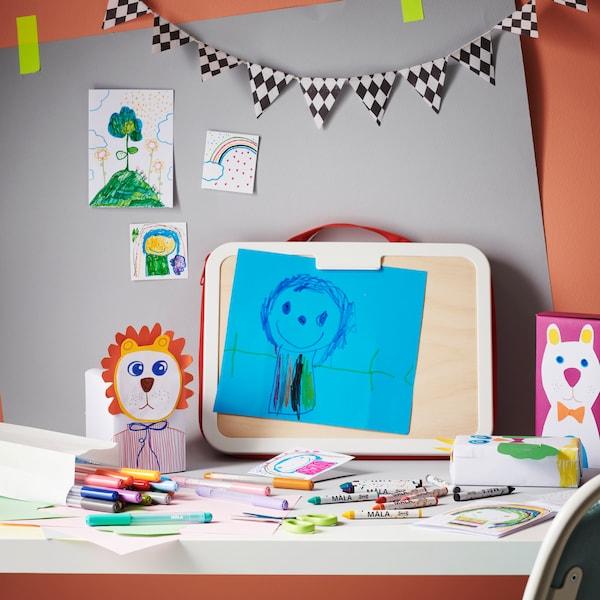 Pouzdro na výtvarné potřeby, pastelky, papíry a další potřeby na stole.
