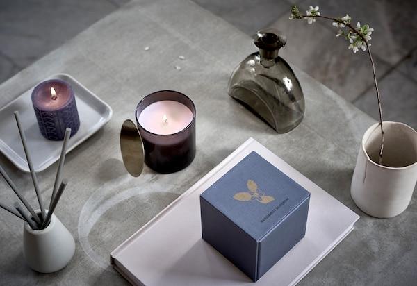 Povrch so symetricky usporiadanými vonnými sviečkami, pohárom s kvitnúcou vetvičkou a podobnými dekoráciami.
