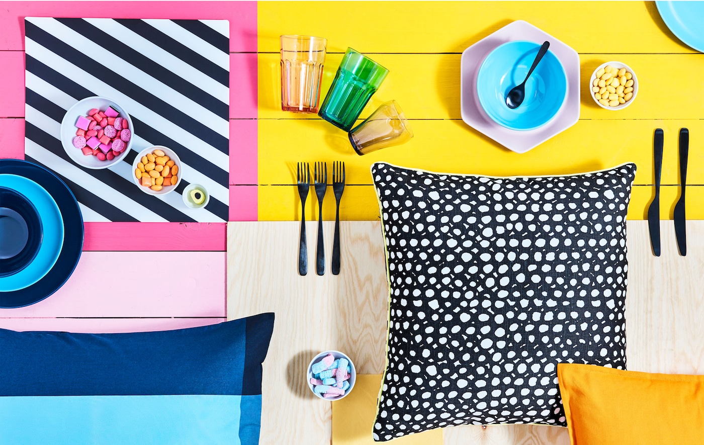 Powierzchnia w jaskrawych kolorach z różnorodną zastawą stołową, miskami z cukierkami i wzorzystymi poduszkami.