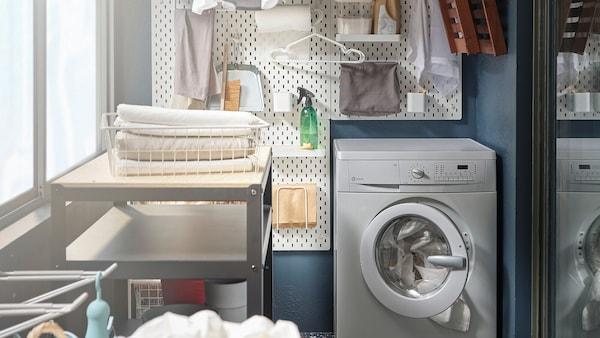 Práčovňa vytvorená v malom priestore balkónu pozostávajúca z práčky, sušiakov a nástennej police.