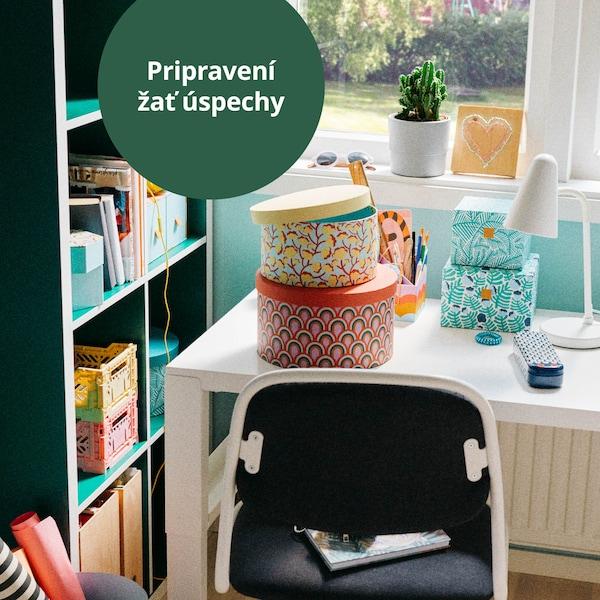 Pracovný stôl pre dieťa so stoličkou, na stole je biela lampa a úložné krabice.