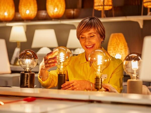 Pracownik sklepu wkręcający żarówkę na dziale oświetlenia.