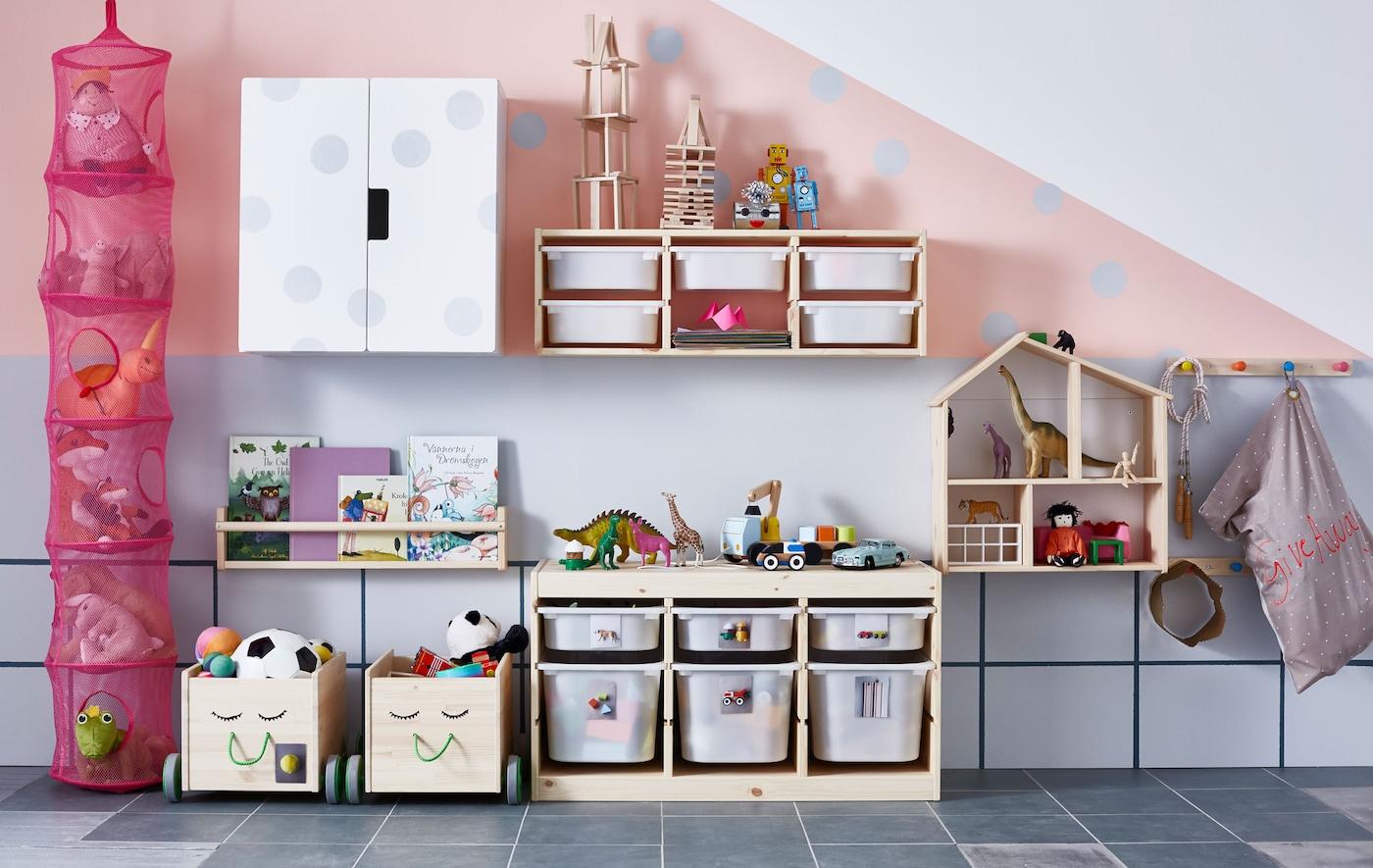 Praktische Spielzeugaufbewahrung aus Holz an der Wand eines grau-rosanen Kinderzimmers
