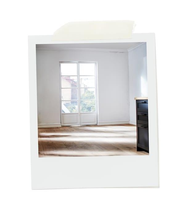 Prázdná místnost zalitá sluncem, bílé stěny, velké francouzské okno do zahrady.