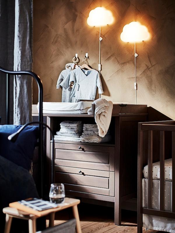 Přebalovací stůl SUNDVIK umístěný v ložnici se dvěma nástěnnými lampami LED UPPLYST a dětským oblečením zavěšeným na stěně nad stolem.