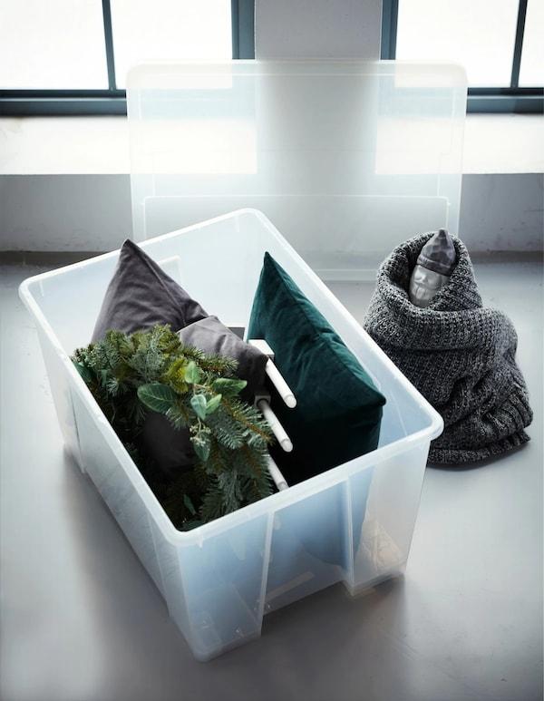 Precisa de ideias de arrumação para as suas decorações depois das festas? Coloque os artigos volumosos numa caixa grande. Use almofadas macias para criar um efeito amortecedor. Na IKEA, pode encontrar muitas caixas grandes, como a caixa SAMLA em plástico transparente. Também tem rodízios!