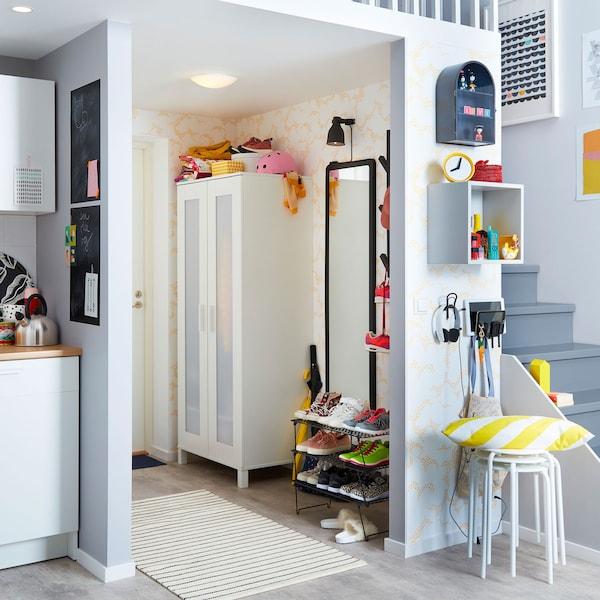 Predsoblje s crnim IKEA GREJIG mrežastim stalkom za obuću i malim bijelim ANABODA ormarom.