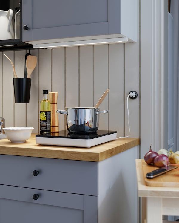 Prenosna indukcijska ploča na drvenoj radnoj ploči. Lonac od nerđajućeg čelika nalazi se na indukcijskoj ploči, a ulje i bela činija su pored.