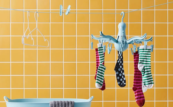 PRESSA octopus clothes hanger with socks on a yellow backdrop