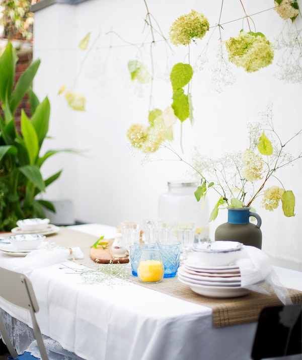 Prestieranie vo vidieckom štýle s taniermi, pohármi a vázou s kvetmi.