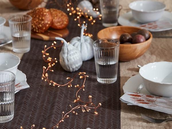 Prestretý stôl, na hnedom obruse HÖSTKVÄLL leží svetelná reťaz STRÅLA, dekorácie – tekvice a poháre VARDAGEN.