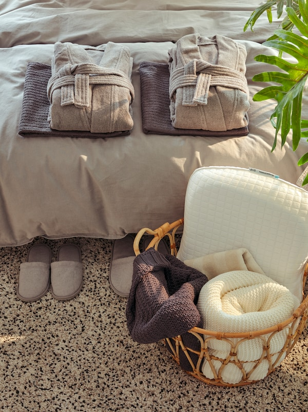Prezentare de tip hotel a unor halate de baie ROCKÅS și prosoape curate împăturite pe un pat. Un coș SNIDAD cu pături și o pernă.
