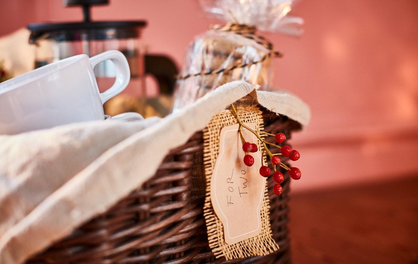 Prezentowy kosz z owiniętymi celofanem herbatnikami, filiżankami, zaparzaczem i dekoracjami.
