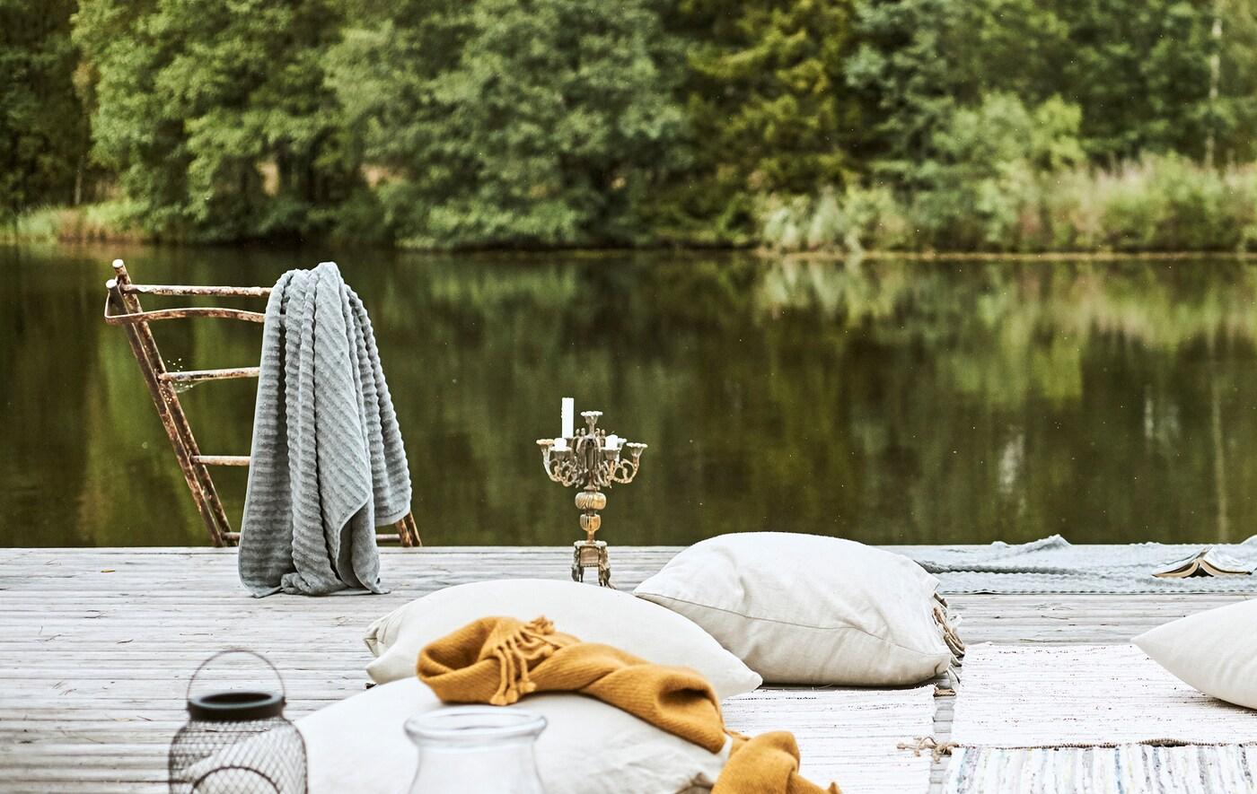 Причал біля озера, подушки та килимки розстелені у бедуїнському стилі, на ржавій драбині висить сірий рушник, поруч канделябр.