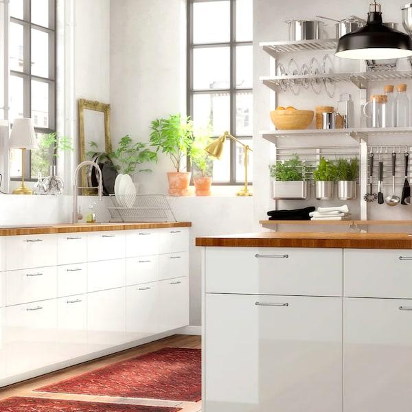 Priestranná biela kuchyňa s drevenou pracovnou doskou.