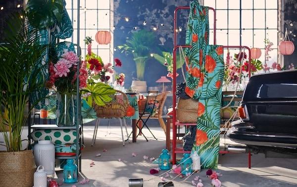 Priestranný interiér v industriálnom štýle pripravený na oslavu s textíliami, dekoráciami, rastlinami a zadnou časťou auta s plechovkami.