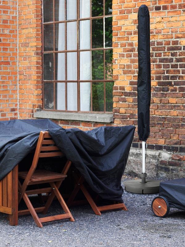 Prikaz drvenog vanjskog stola i stolica koji se nalaze ispod crne navlake, a pored njih se nalazi i sklopljeni suncobran na koji je navučena navlaka.