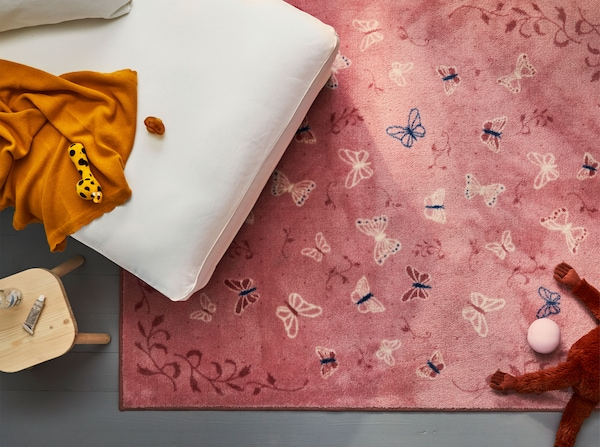 Prikaz IKEA SÅNGLÄRKA tepiha niskog flora s rozim leptirima iz zraka. Tepih je djelomično skriven ispod bijele počivaljke.